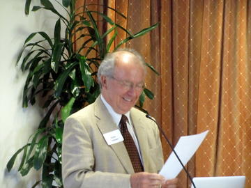 UMRA Presdent John Adams anticipates the punchline of a joke he is telling to the April 2014 audience