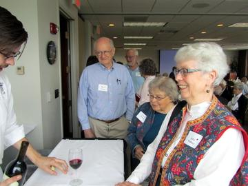 Julia Wallace, Carol Urness, Ted Farmer and others take advantage of wine service at the May Festive Luncheon and Annual Meeting