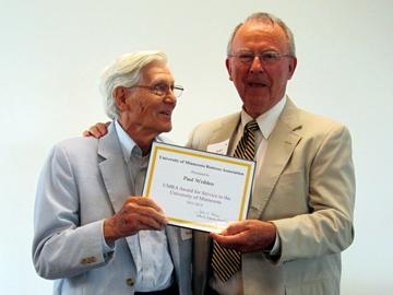 Paul Weiblen accepts the 2014 Award for Service to the University from President John Adams