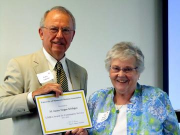 President John Adams presents the 2014 Award for Service to the Community to Jan Hogan Schiltgren at the May Luncheon