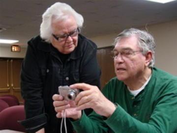 Lorraine Berger gets help from Hal Miller, UMRA Past President at UMRA Photo