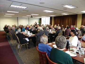 A full house listens to announcements by John Adams, just before the February 2016 luncheon