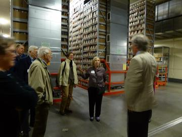 Donna Peterson addresses Tim Johnson, with a group in the depths of the Library Archives, Sept 27